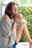 Mujer que se sienta por la ventana en casa que huele una taza de café fresca Imagen de archivo libre de regalías