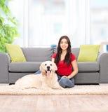 Mujer que se sienta por un sofá con su perro en casa Fotos de archivo