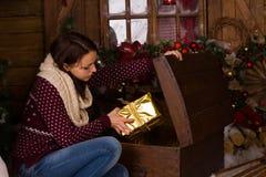 Mujer que se sienta que consigue presentes de oro de tronco Fotos de archivo libres de regalías