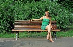 Mujer que se sienta solamente en banco Imagen de archivo