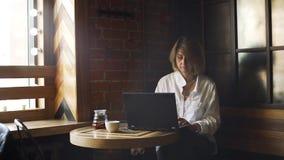 Mujer que se sienta solamente en café y que trabaja en el ordenador portátil almacen de video