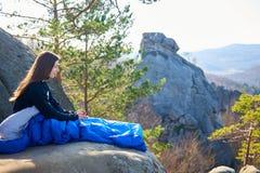 Mujer que se sienta solamente en saco de dormir en roca grande y la sonrisa de la montaña imagen de archivo
