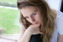 Mujer que se sienta solamente por la ventana fotos de archivo