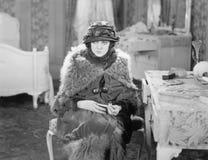 Mujer que se sienta vestido todo para arriba en su dormitorio que parece desanimado (todas las personas representadas no son viva foto de archivo