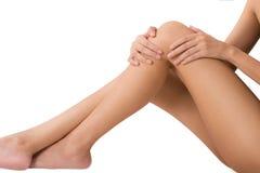 Mujer que se sienta y que lleva a cabo la pierna larga sana hermosa con el masaje de la rodilla y del muslo en área del dolor Foto de archivo
