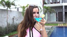 Mujer que se sostiene de cristal con el margarita del coctail y que bebe en el chalet de lujo almacen de video