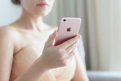 Mujer que se sostiene en el iPhone 6 S Rose Gold de la mano Fotos de archivo libres de regalías