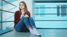 Mujer que se sostiene en la taza de las manos de café con la leche que se sienta en el piso metrajes