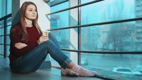 Mujer que se sostiene en la taza de las manos de café con la leche que se sienta en el piso cerca de la ventana metrajes