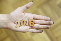 Mujer que se sostiene en números de madera de un Año Nuevo 2016 de la mano Foto de archivo
