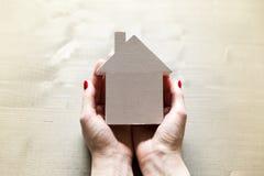 Mujer que se sostiene en pequeña casa modelo blanca de las manos como muestra del prot fotos de archivo libres de regalías