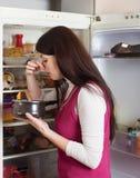 Mujer que se sostiene la nariz debido a mún olor cerca del refrigerador imagen de archivo