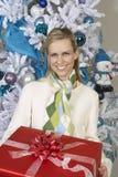 Mujer que se sostiene presente en Front Of Christmas Tree Imágenes de archivo libres de regalías