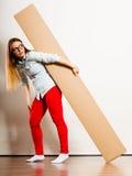 Mujer que se traslada al apartamento que lleva la caja pesada Imágenes de archivo libres de regalías