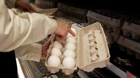 Mujer que selecciona el huevo en el departamento de la producción del colmado metrajes