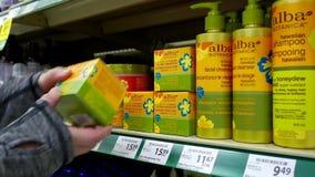 Mujer que selecciona la crema hidratante sin aceite del botanica Alba metrajes