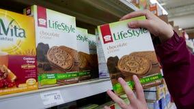 Mujer que selecciona la galleta del chocolate del plátano de la forma de vida almacen de video