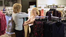 Mujer que selecciona la ropa mientras que hace compras para la ropa almacen de video