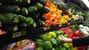 Mujer que selecciona las pimientas verdes en colmado metrajes