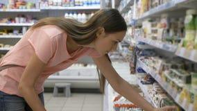 Mujer que selecciona los productos lácteos en refrigerador en el departamento del ultramarinos de alameda de compras