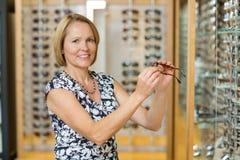 Mujer que selecciona los vidrios en el óptico Store imagenes de archivo