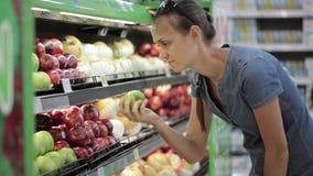 Mujer que selecciona manzanas frescas en colmado almacen de metraje de vídeo