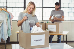Mujer que separa la ropa de la caja de la donación Imagen de archivo