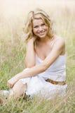 Mujer que sienta al aire libre la sonrisa Imagenes de archivo