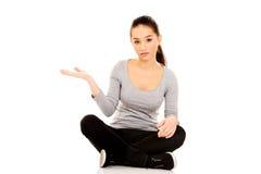 Mujer que sienta legged cruzado con la mano abierta Foto de archivo
