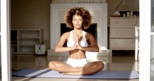 Mujer que sienta a Lotus Position On Floor Fotos de archivo