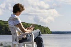 Mujer que sienta una lectura en una silla por el lago Imagen de archivo