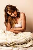Mujer que siente enferma con el dolor de estómago en cama - duela en estómago fotografía de archivo