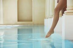 Mujer que siente la temperatura del agua por el Poolside Imagenes de archivo