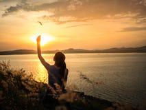 Mujer que siente libremente en la puesta del sol fotos de archivo libres de regalías