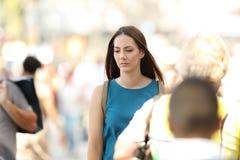Mujer que siente solamente que camina entre la gente Fotos de archivo