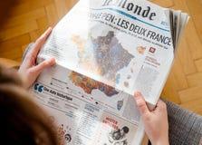 Mujer que sigue leyendo Le Monde con Emmanuel Macron y Marine Le Pen Fotos de archivo