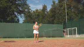 Mujer que sirve la bola para un juego del tenis en corte almacen de metraje de vídeo