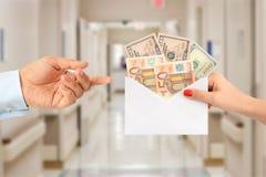 Mujer que soborna a un hombre con un sobre lleno de dinero que sugiere un sistema sanitario corrupto fotos de archivo