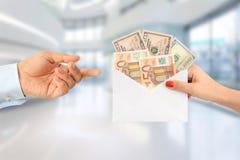 Mujer que soborna a un hombre con un sobre lleno de dinero que sugiere un sistema sanitario corrupto foto de archivo