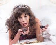 Mujer que solloza en Tiara Drinking Wine y chocolates que abarrotan adentro Foto de archivo libre de regalías