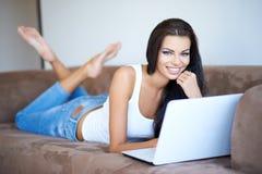 Mujer que sonríe como ella se relaja con su ordenador portátil Foto de archivo
