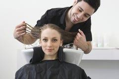 Mujer que sonríe con el peluquero que examina su pelo en el salón fotografía de archivo libre de regalías