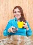 Mujer que sonríe con el telecontrol de la TV Imagen de archivo libre de regalías
