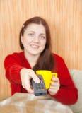 Mujer que sonríe con el telecontrol de la TV Fotografía de archivo libre de regalías