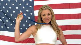 Mujer que sonríe con la medalla en manos metrajes