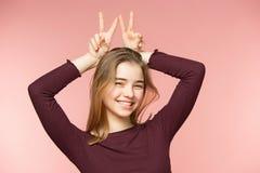 Mujer que sonríe con sonrisa perfecta y los dientes blancos en el fondo rosado del estudio y que mira la cámara Fotos de archivo libres de regalías