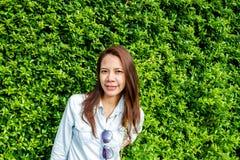 Mujer que sonríe en el parque contra el contexto de la hoja verde Fotos de archivo libres de regalías