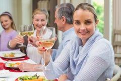 Mujer que sonríe en la cámara mientras que sostiene un vidrio de vino Foto de archivo