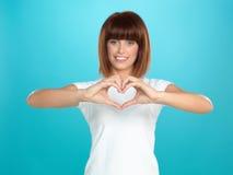 Mujer que sonríe haciendo dimensión de una variable del corazón con las manos imagenes de archivo