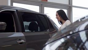 Mujer que sonríe a la cámara, mientras que examina los coches en venta en la representación almacen de metraje de vídeo